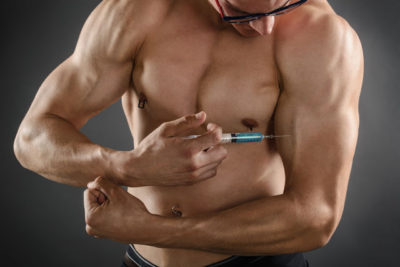 42262046 - close up of a muscular man injecting himself with steroids